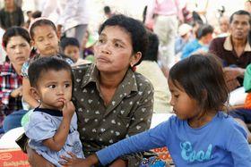 2人の子どもと共にエイズウイルス感染が確認された女性(中央)=2016年3月、カンボジア西部バタンバン州ロカ(共同)