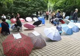 人民公園の〝お見合い広場〟。良縁を求め、プロフィルを貼った傘が並ぶ。そばに陣取る人々の多くは家族=2016年10月、中国・上海(共同)