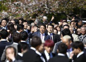 「桜を見る会」で手を振る安倍首相(中央)=4月、東京・新宿御苑