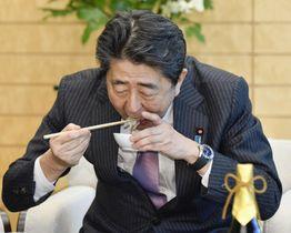 「下関ふく連盟」から贈られた天然トラフグの刺し身を試食する安倍首相=19日午後、首相官邸