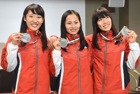 トランポリンの世界選手権から帰国し、メダルを手に笑顔の(左から)森ひかる、岸彩乃、高木裕美=14日午後、東京都内のホテル