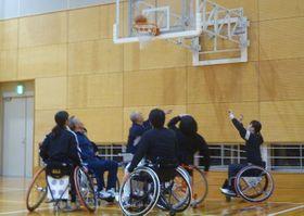 車いすバスケットボールに取り組む参加者=長崎市小江原5丁目、県警察学校体育館