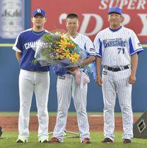 花束を渡した中日・松坂(左)と横浜DeNA・小池コーチに挟まれ涙をこらえる後藤=横浜