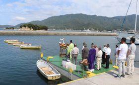 弁天島(左奥)を望むボート乗り場で安全を祈願する関係者=香川県小豆島町苗羽
