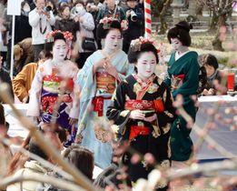 京都・北野天満宮の「梅花祭」で、参拝客をもてなす舞妓ら=25日午前