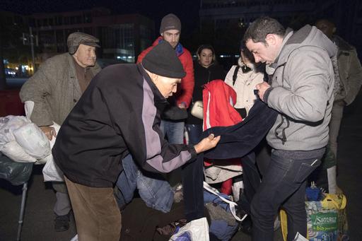 木曜の夜、「マロウド」活動の青年(右)が持ち込んだ冬物衣料を品定めする路上生活者の男性=2018年11月、フランス・リヨン(共同)
