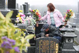 先祖や故人をしのび、墓参りをする家族連れ=21日午前、宮崎市・みたま園