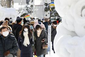「さっぽろ雪まつり」会場をマスク姿で歩く人たち=4日、札幌・大通公園