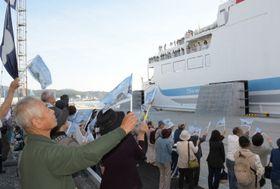 旗を振ってフェリーの入港を祝う市民ら=23日午前5時53分、宮古市の宮古港フェリーターミナル