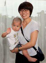 周東総合病院を退院し、母の美緒さん(右)に抱かれ元気な様子を見せる理稀ちゃん(20日午後3時7分、撮影・山下悟史)