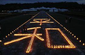 沖縄全戦没者追悼式の前夜祭で、ろうそくの火をともし浮かび上がった「平和」の文字=22日夕、沖縄県糸満市の平和祈念公園