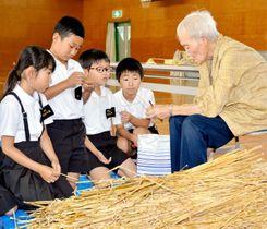 (上)玉井さんからわら笛の作り方を教わる田野小児童(下)玉井さんが作った馬の飾りやかご