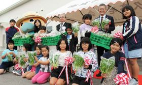 久高島野菜工場前で初出荷の野菜を手にほほえむ子どもたち=17日、南城市知念久高