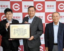 宇佐見局長から表彰状を受ける篠木村長(中央)。右は松本副会長