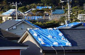 台風15号の影響で被害を受けブルーシートが張られた家屋=17日午後、千葉県鋸南町