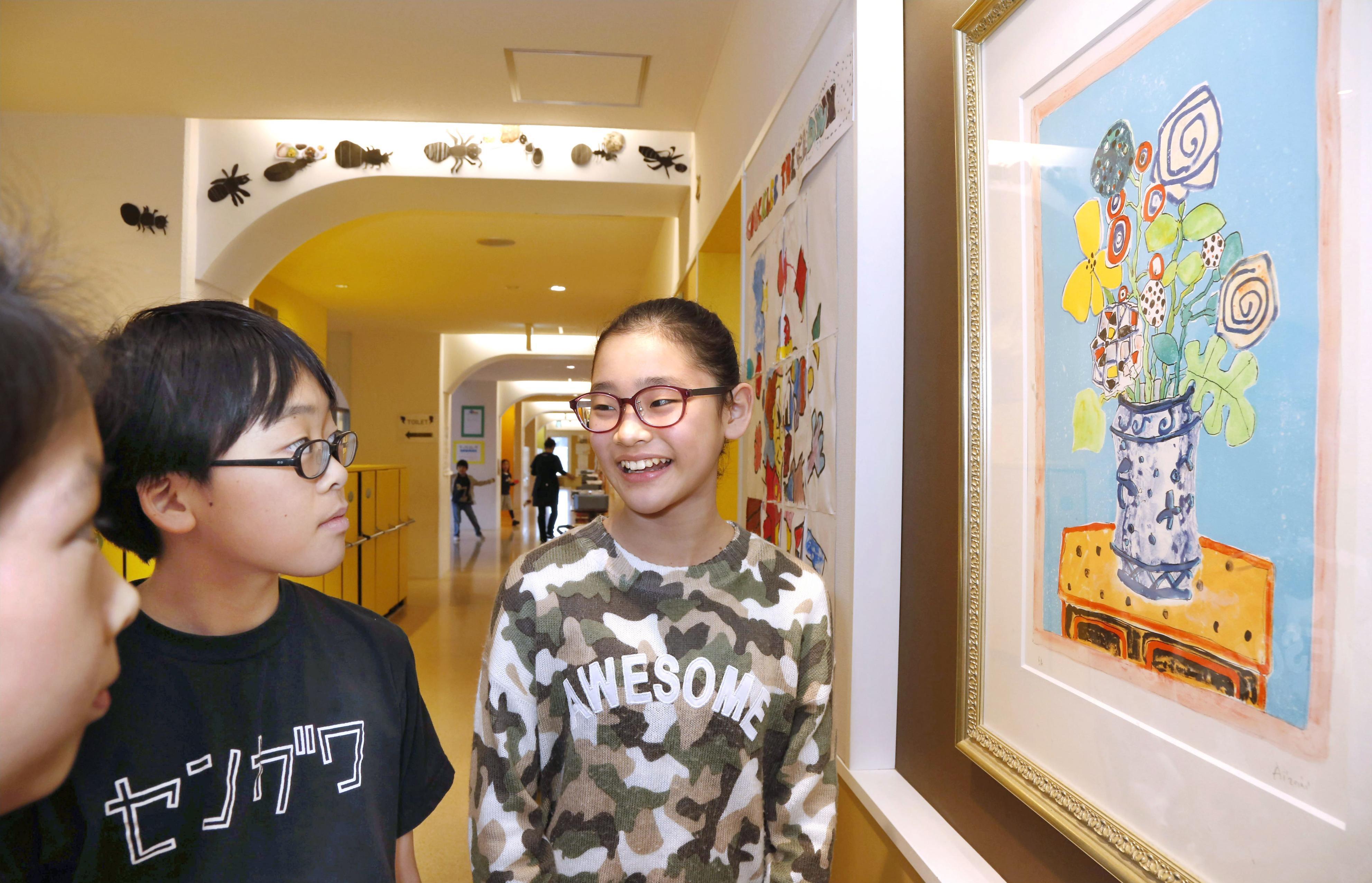 LCA国際小学校の校舎内に飾られた絵画を見る桜田麗実菜(右)ら=相模原市