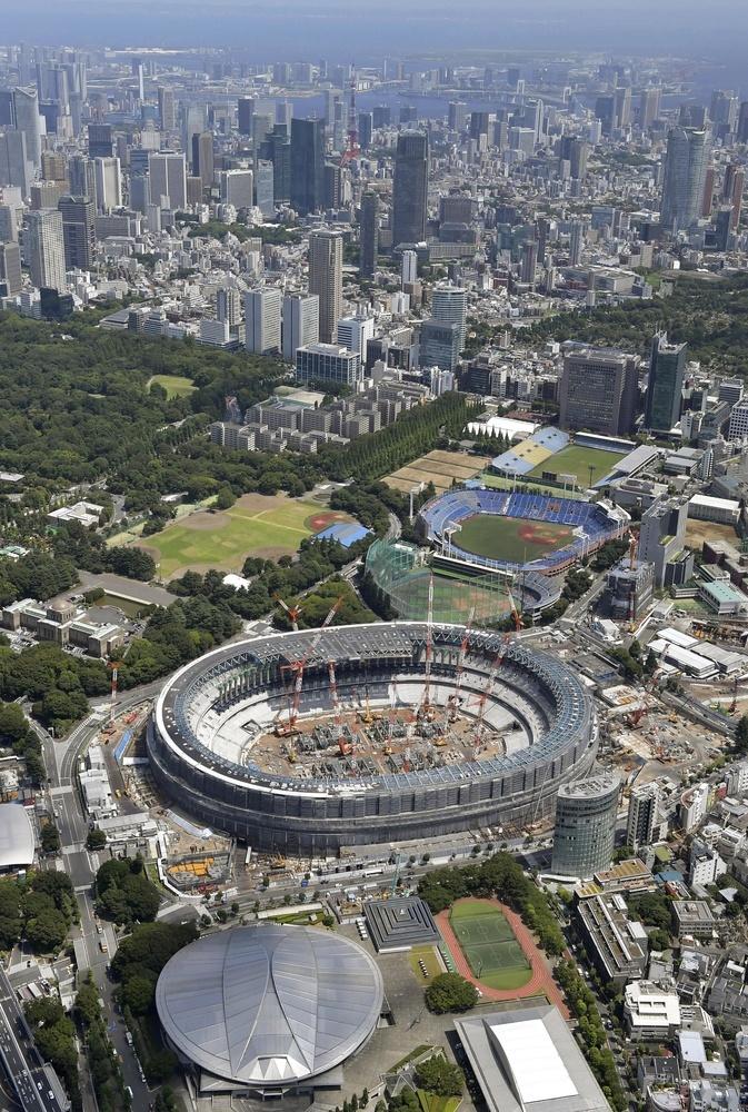 工事が進む新国立競技場(中央)。手前の円形屋根の建物は卓球会場の東京体育館。上は競技会場が集まる臨海部=7月、東京都内