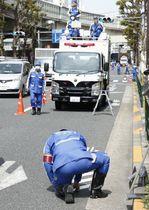 道路の一部を通行止めにして、事故現場の状況を調べる捜査員=22日午前、東京都豊島区