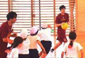 子どもらとミニゲームをする藤井選手(右奥)と長谷川選手(左端)