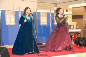 【買い物客らの前で歌う「気軽にクラシックとミュージカル」の2人=鈴鹿市算所2丁目の鈴鹿ハンターショッピングセンターで】