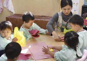 紙の工作をして遊ぶ東京朝鮮第六幼初級学校の園児ら=16日、東京都大田区