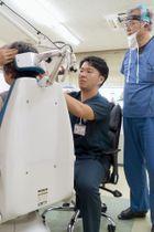 神崎裕士(右)の指導を受けながら診察する内科医・上垣内隆文