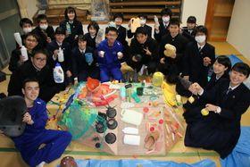 漂着ごみをカメの甲羅に見立てたベニヤ板に貼り付け、モニュメントを制作する生徒たち=五島高