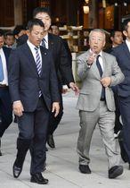 明治神宮参拝後に、会話を交わしながら歩く星稜の林和成監督(左)と明徳義塾の馬淵史郎監督=14日午後、東京都渋谷区