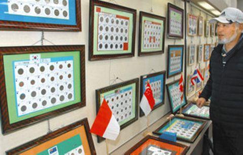 世界各国の硬貨や紙幣を紹介する三戸さん=岡崎市の岡崎信用金庫本店で