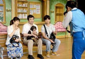 動物ショーの終演後、見物客と笑顔で記念撮影する宮沢厚さん(左から2人目)とチンパンジーのプリンちゃん=阿蘇市