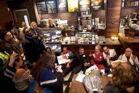米フィラデルフィアのスターバックス店内で座り込む抗議運動の参加者ら=16日(ロイター=共同)