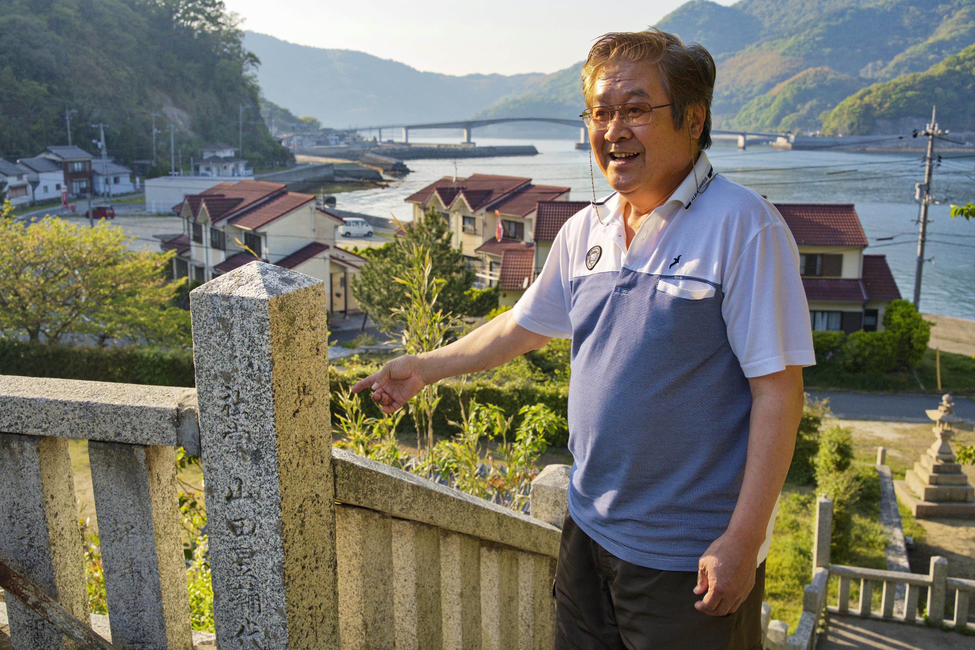 数多くの移民を出した沖家室島の神社を案内する日本ハワイ移民資料館館長の木元真琴。玉垣にはハワイ移民らの名前が刻まれている=山口県周防大島町