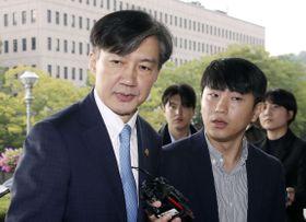 14日、ソウル近郊の法務省庁舎前で報道陣の取材に応じる韓国のチョ・グク法相(左)(聯合=共同)
