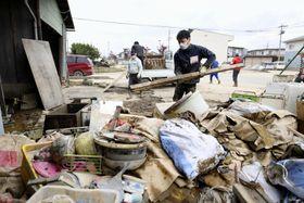 浸水被害のあった住宅の災害ごみを運ぶボランティア=21日午後、長野市