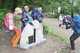 除幕された記念碑と写真を撮る登山客