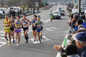 青空の下、沿道の声援を受けて力走する選手たち=南さつま市金峰町池辺