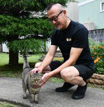 数年前に避妊手術を施した猫と触れ合う新山勉代表。カットされた右耳の先が手術した目印