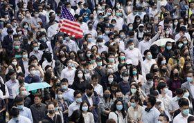 金融街セントラルで「五大要求」などの実現を求め、デモ行進する人々=14日、香港(共同)