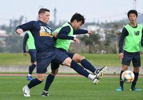 キャンプ初日から激しく競り合うフェルナンド・トーレス選手(左)=沖縄県の読谷村陸上競技場