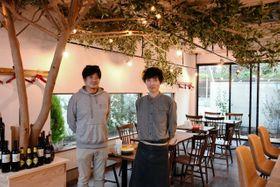 オリーブの木が飾られた店内に立つシェフの八木孝明さん(右)とオーナーの今木雄三さん=レストラン「ラ・フォルケッタ」