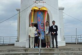 本年度1万人目の来場者となった伊賀七翔君(左から2人目)と父の大貴さん(同3人目)