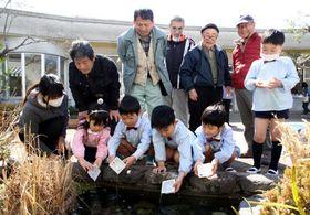 地元の園児と一緒にホタルの幼虫を放流する「瀬野川ホタルの会」のメンバーたち