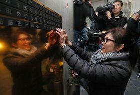 「慰霊と復興のモニュメント」に母の梅本美代子さんの名前が刻まれた銘板を取り付ける同免木美佐さん=17日午後、神戸市(代表撮影)