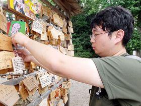 境内の絵馬掛け所に絵馬を奉納する男性=21日午後、久喜市鷲宮の鷲宮神社