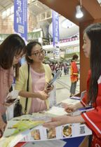 日本観光について説明を受ける江潔莎さん(中央)=21日、中国・広州(共同)