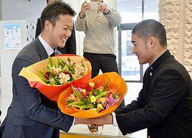 山形中央高の後輩から花束を受け取る斎藤友貴哉投手(左)=山形市・同校