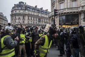 警官隊の前を行進する黄色いベスト運動の参加者たち=15日、パリ(ゲッティ=共同)
