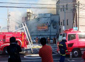 白煙を上げる建物と消火活動に当たる消防隊員ら=17日午後2時25分、さいたま市大宮区(近隣住民提供、画像の一部をモザイク加工しています)