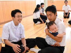 赤ちゃんを抱っこする生徒=丸亀市大手町、丸亀東中
