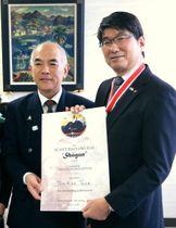 ワット氏の代理者である山崎さんから賞状を受け取る田上市長(右)=長崎市役所